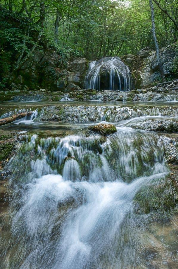 Uma cascata de cachoeiras bonitas no desfiladeiro haphal Península crimeana Paisagem tropical foto de stock