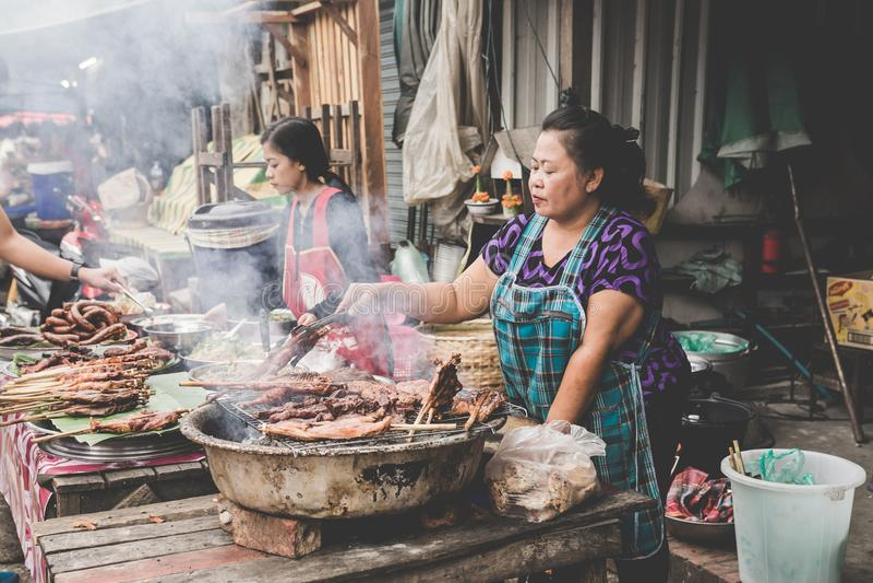 Uma cena típica de uma mulher local do tribo do monte que cozinha em um assado em uma tenda da borda da estrada em Luang Prabang, fotos de stock