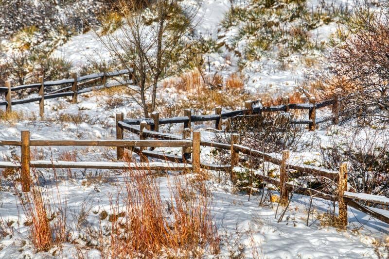 Uma cerca de trilho nevado pitoresca da separação do rancho com esfrega e escova fotografia de stock royalty free