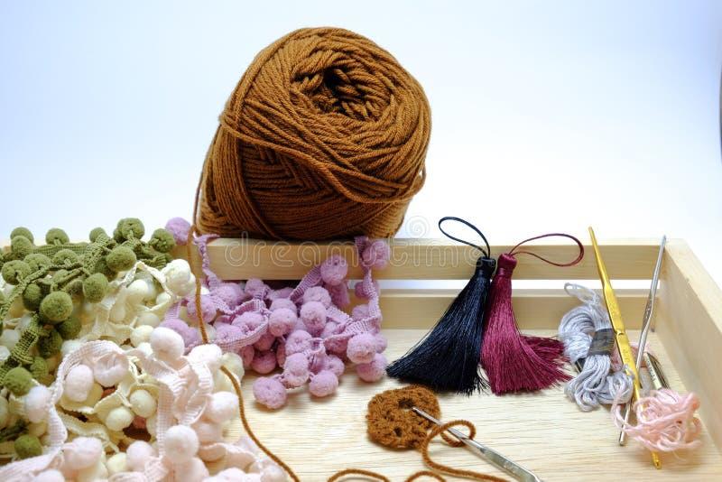 Uma cesta de faz crochê o fio, a borla e a agulha de crochê fotografia de stock royalty free