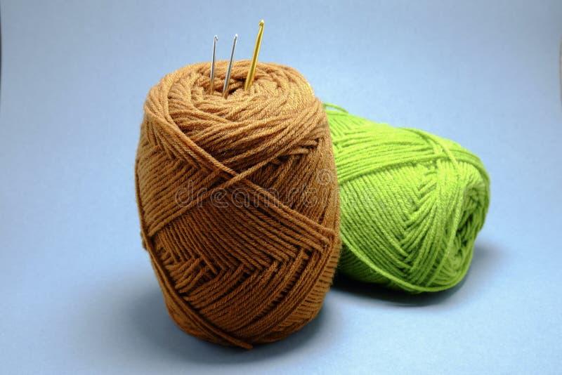 Uma cesta de faz crochê o fio, a borla e a agulha de crochê imagens de stock royalty free