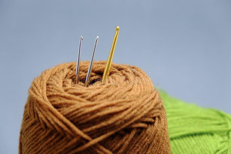 Uma cesta de faz crochê o fio, a borla e a agulha de crochê foto de stock royalty free