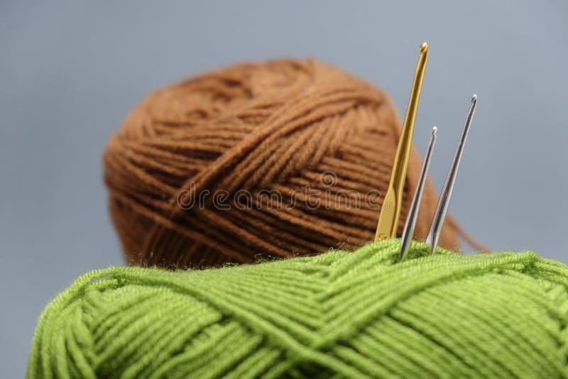 Uma cesta de faz crochê o fio, a borla e a agulha de crochê imagem de stock