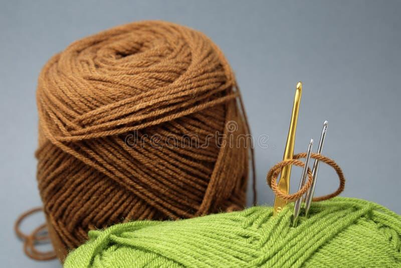 Uma cesta de faz crochê o fio, a borla e a agulha de crochê fotos de stock royalty free