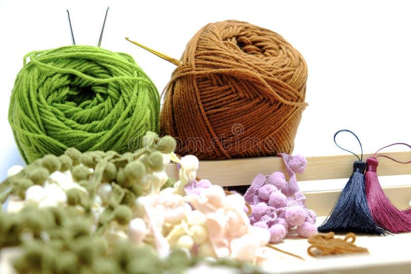Uma cesta de faz crochê o fio, a borla e a agulha de crochê foto de stock