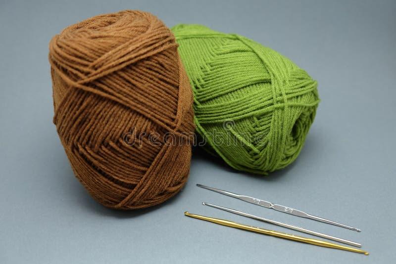 Uma cesta de faz crochê o fio, a borla e a agulha de crochê imagem de stock royalty free