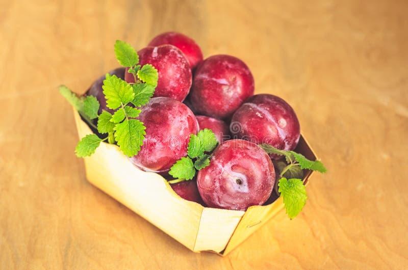 Uma cesta pequena com as ameixas vermelhas brancas imagens de stock