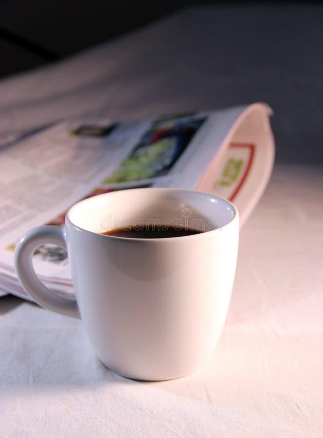 Uma chávena de café e um jornal fotografia de stock royalty free