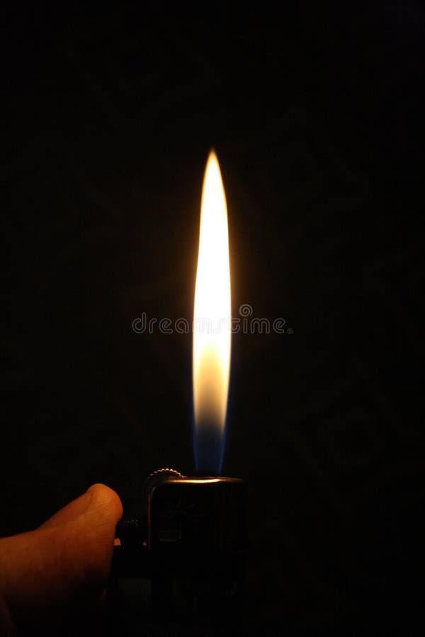 Uma chama mais clara iluminou-se acima em uma sala escura imagens de stock