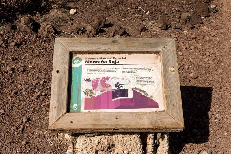 Uma chapa da informação ao lado do depósito do relógio na reserva natural especial da montagem vermelha, EL Medano, Tenerife, Esp fotografia de stock