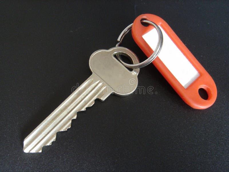 Uma chave com um anel e um Tag fotografia de stock royalty free