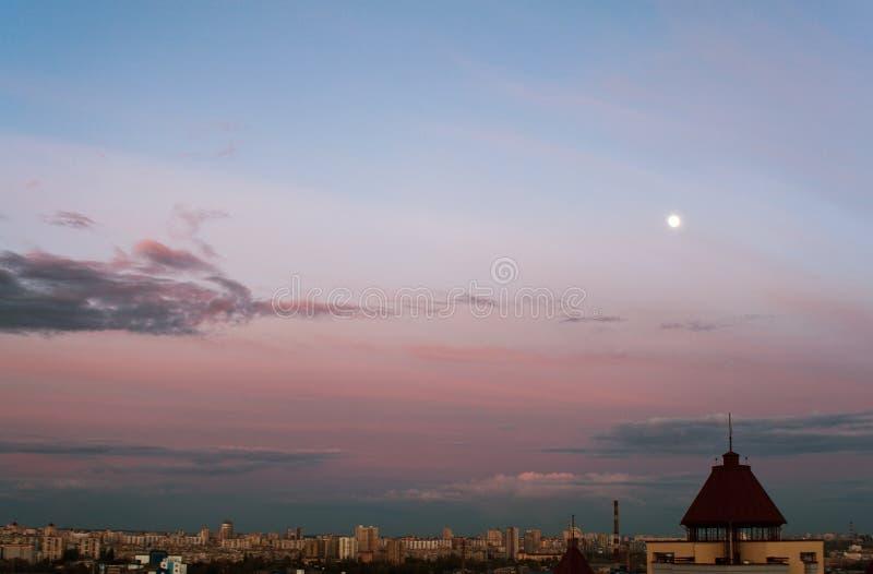 Uma cidade Cloudscape com lua imagem de stock