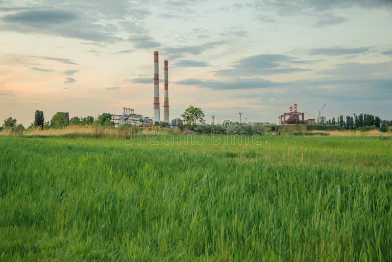 Uma clareira verde no fundo da zona industrial imagens de stock