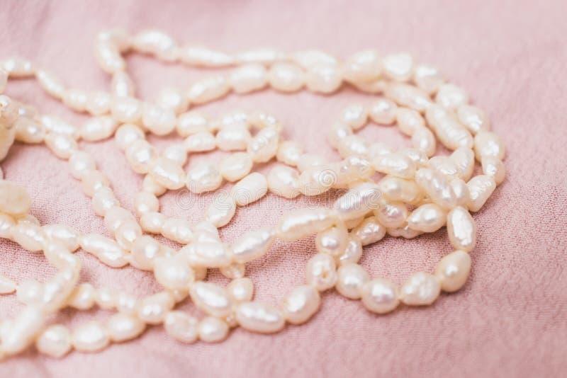 Uma colar da pérola, bijouterie no fundo bege puro delicado da tela imagem de stock