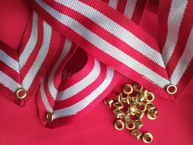 Uma coleção de ilhotas de ouro e três fitas de medalhão listradas fotos de stock