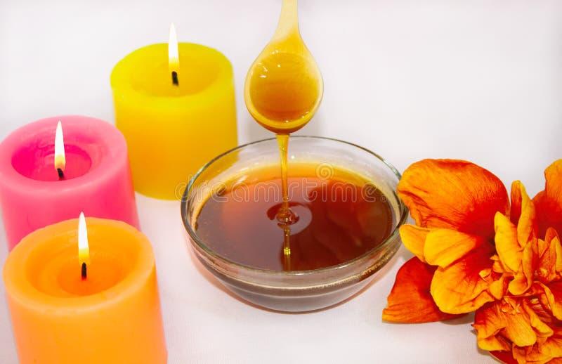 Uma colher de madeira com açúcar líquido, para o epilation Com mel líquido Close-up Aromaterapia, velas foto de stock royalty free