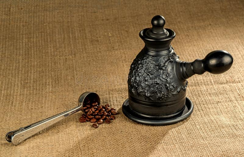 Uma colher de medição de aço com cafeteira da argila imagem de stock royalty free