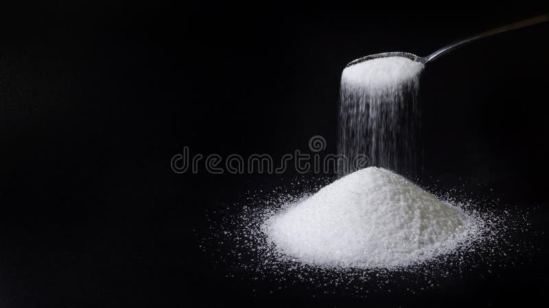 Uma colher do chá derrama o açúcar dentro a uma pilha fotos de stock