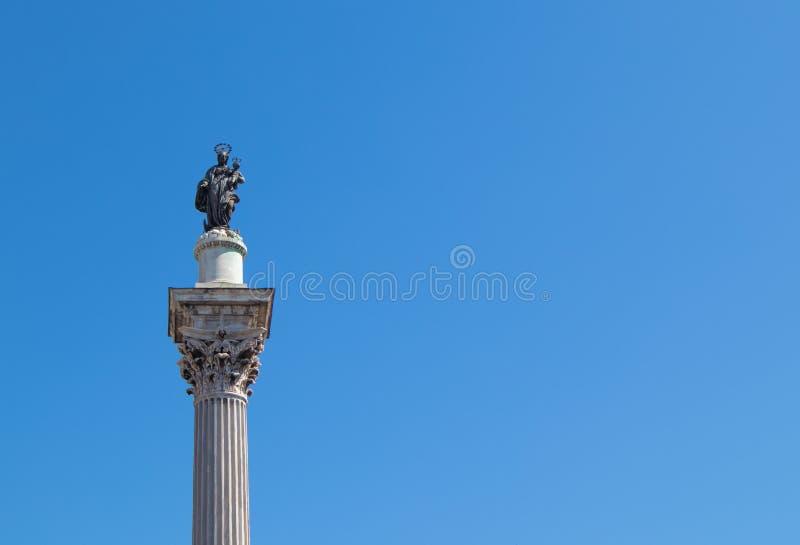 Uma coluna corintiana com Madonna e a criança no topo e um céu azul no fundo imagens de stock