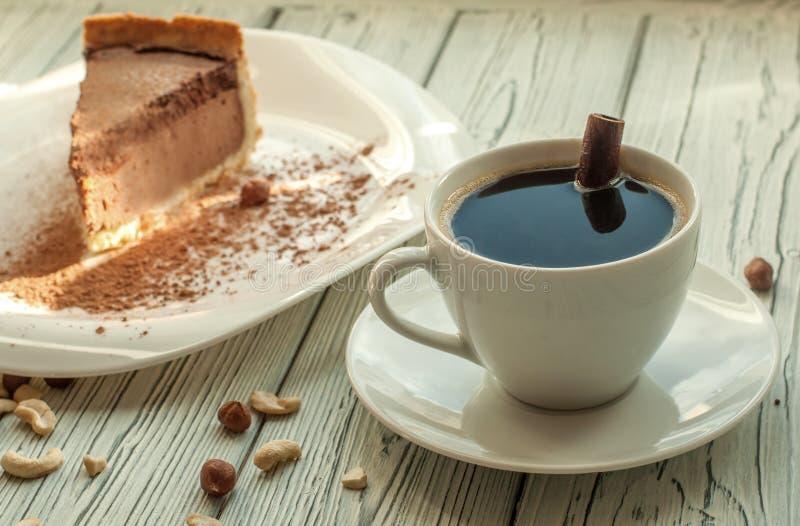 Uma composição com um copo do café preto e uma paz de um bolo de queijo do chocolate decorado com pó e porcas de cacau fotografia de stock