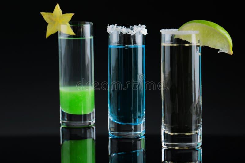 Uma composição de três bebidas coloridas do tiro Cocktail alcoólicos com frutos decorativos em um fundo preto cópia foto de stock