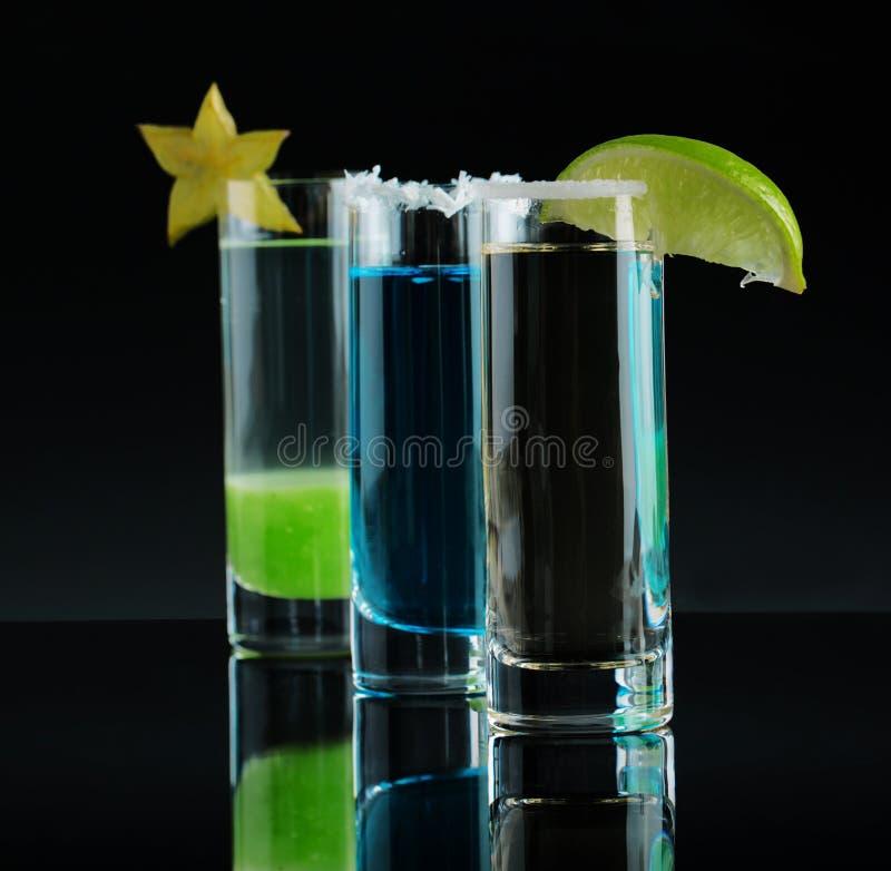 Uma composição de três bebidas coloridas do tiro Cocktail alcoólicos com frutos decorativos em um fundo preto cópia foto de stock royalty free