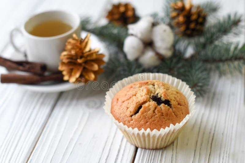 Uma composição do Natal com um copo do chá, de queques caseiros, de cones, de galhos da pele e de varas de canela imagem de stock royalty free