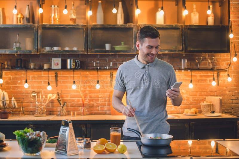 Uma comunicação do telefone da preparação da refeição do vegetariano do homem novo imagem de stock
