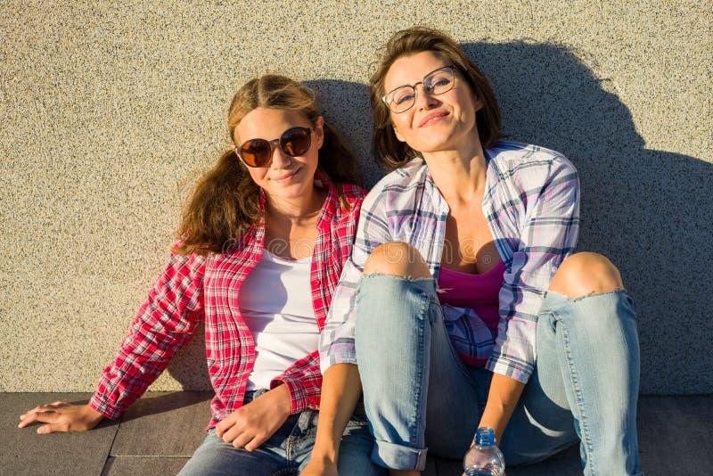 Uma comunicação entre a mãe e a filha adolescente Fundo do por do sol da cidade fotografia de stock