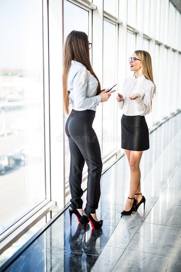 Uma comunicação informal das mulheres de negócio sobre janelas panorâmicos foto de stock