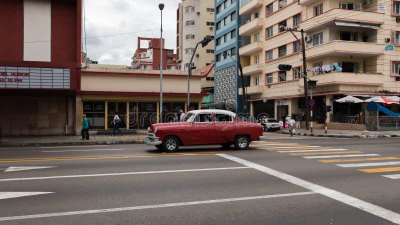Uma condu??o de carro vermelha velha e bonita atrav?s das ruas de Havana imagens de stock