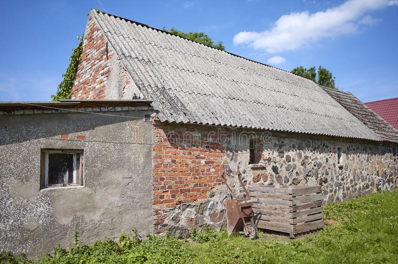 Uma construção abandonada velha com o telhado feito de telhas carcinogênicas do asbesto imagens de stock royalty free