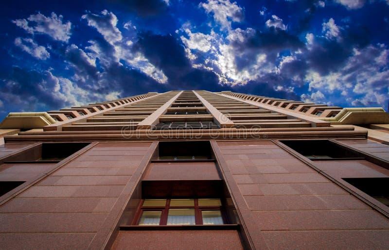 Uma construção alta no céu do fundo com nuvens fotografia de stock royalty free