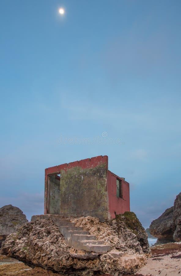 Uma construção arruinada interessante sobre rochas na costa fotografia de stock royalty free