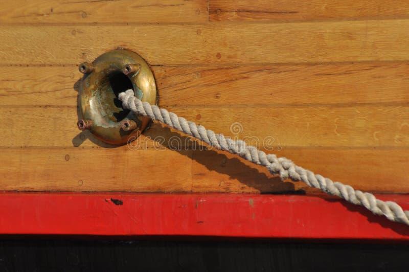 Uma corda da amarração que sai do furo no lado do navio imagem de stock