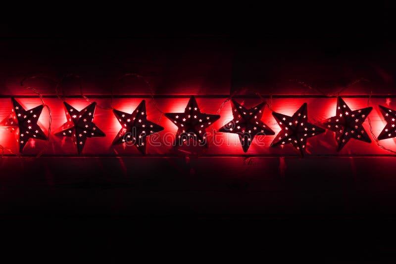 Uma corda de luzes vermelhas dos christams da estrela em um backgroun de madeira escuro imagem de stock royalty free