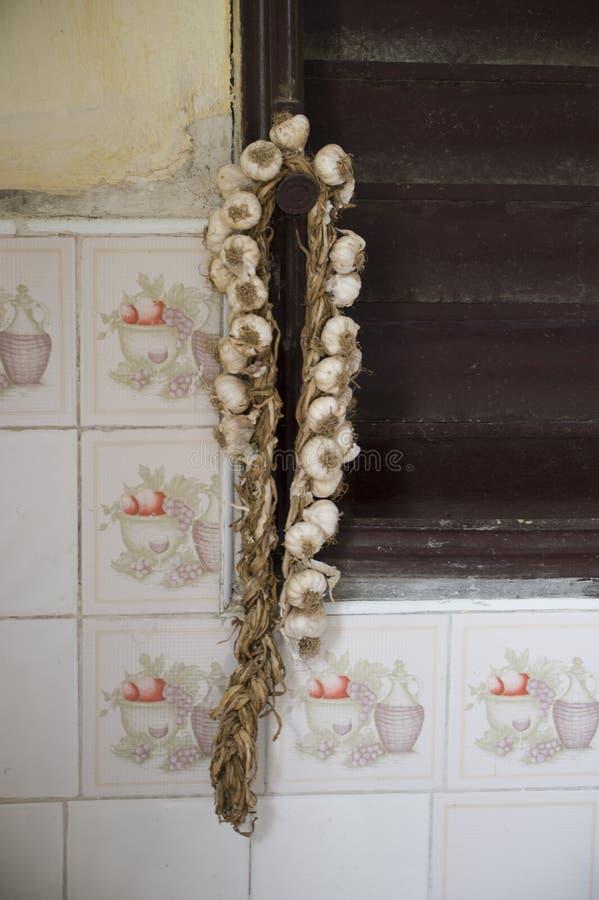 Uma corda do alho e da cebola que penduram fora de uma casa em Cuba foto de stock