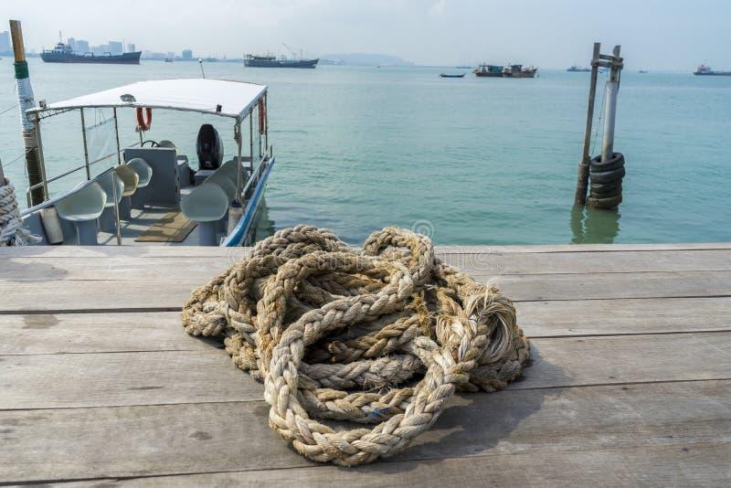 Uma corda enrolado no cais de madeira, o mar e o barco são fundo fotografia de stock