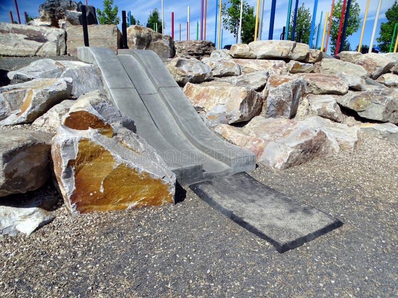 Uma corrediça das crianças concretas em um parque foto de stock royalty free