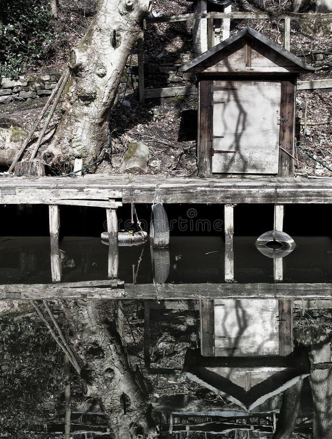 Uma corrida da margem abaixo do molhe de madeira com uma barraca e uma árvore pequenas refletiu na água imóvel fotografia de stock