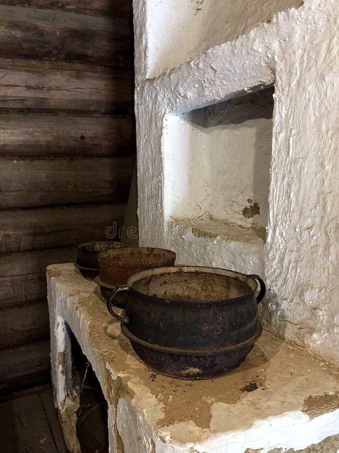 Uma cozinha antiga velha com caldeirões do ferro foto de stock