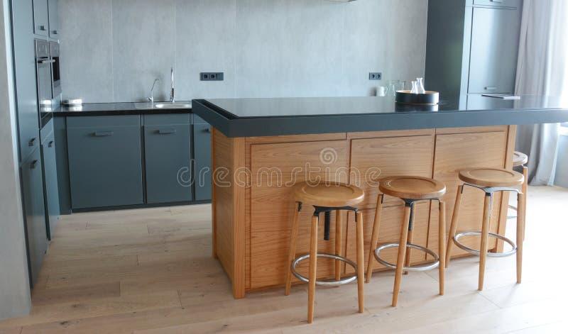 Uma cozinha moderna, com um contraplacado cinza escuro com uma pia de metal com torneira de aço, plugues elétricos montados na pa fotos de stock