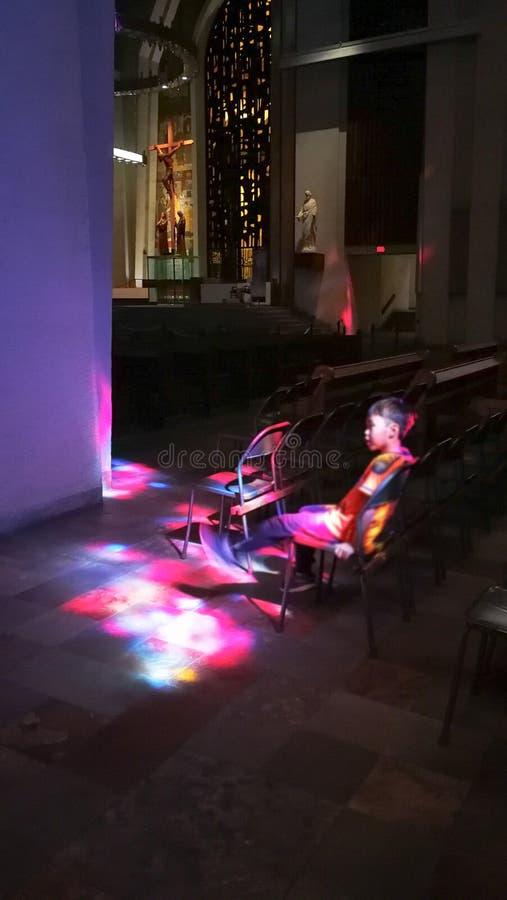 Uma criança é banhada à vista de Jesus sob a igreja É morno e romântico imagem de stock