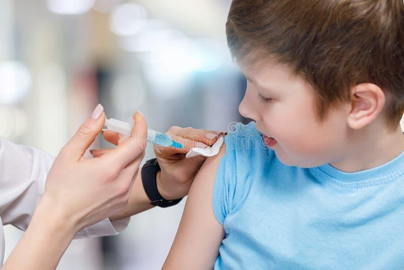 Uma criança adolescente está recebendo uma vacinação preventiva foto de stock
