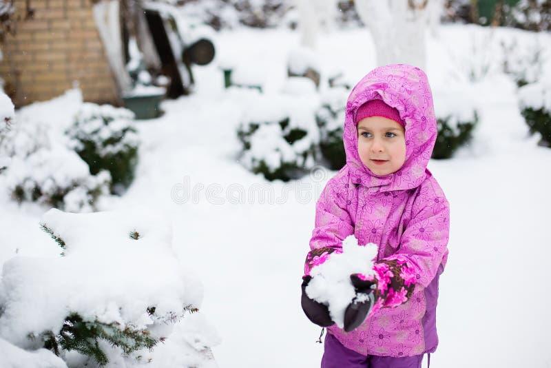 Uma criança alegre esculpe bolas de neve fora em um dia de inverno imagens de stock royalty free