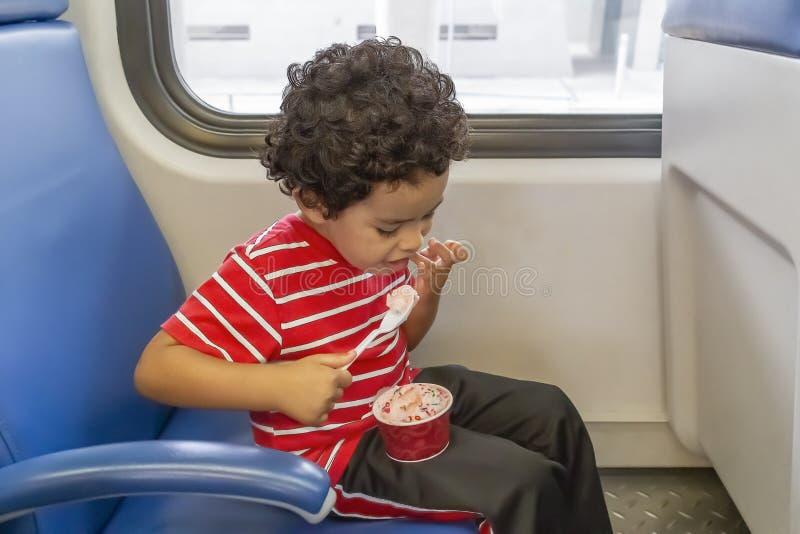 Uma criança aprecia um copo do gelado ao sentar-se no trem foto de stock