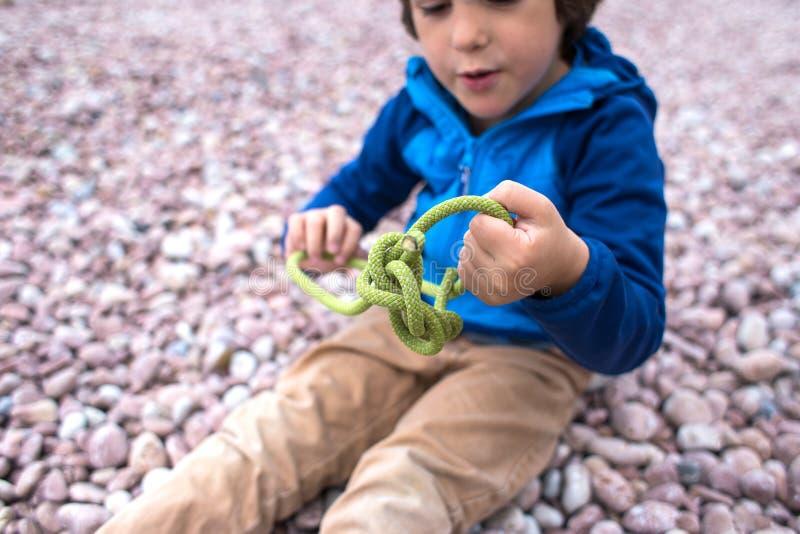 Uma criança aprende fazer malha um nó de uma corda imagens de stock royalty free