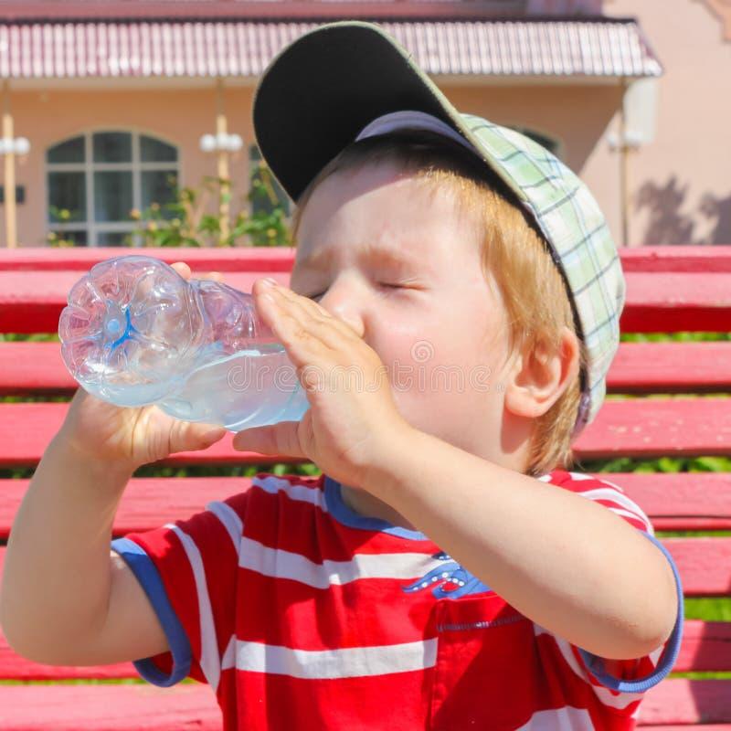 Uma criança bebe a água de uma garrafa A criança, menino, extingue fotos de stock