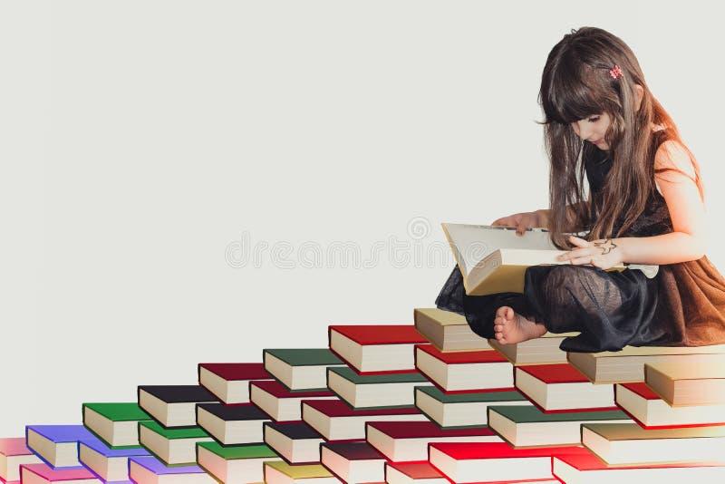 Uma criança bonito pequena sábia da menina em um vestido preto que senta-se na pilha da leitura do livro e que aprende o conhecim fotografia de stock