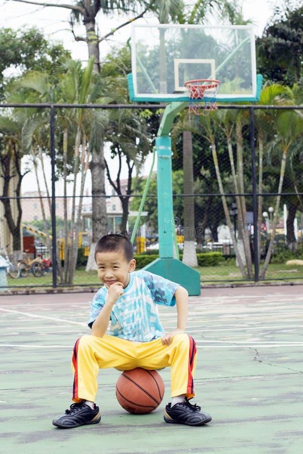 Uma criança chinesa com um basquetebol foto de stock royalty free
